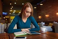 Молодая женщина наблюдает видео на цифровой таблетке во время остатков в современной кофейне Стоковое Изображение