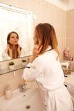 Молодая женщина наблюдая в зеркале стоковое фото rf