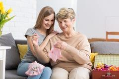 Молодая женщина наблюдая ее бабушку вышивает Стоковые Изображения RF