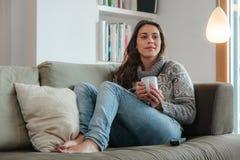 Молодая женщина наблюдая софу tv домашнюю стоковая фотография rf