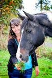 Молодая женщина напольная подающ лошадь Стоковые Изображения