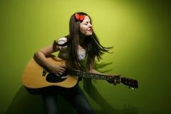 Молодая женщина наслаждается сыграть гитару Стоковое Изображение