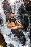 Молодая женщина наслаждаясь в естественном тропическом водопаде стоковые изображения