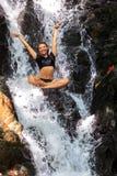 Молодая женщина наслаждаясь в естественном тропическом водопаде стоковое фото