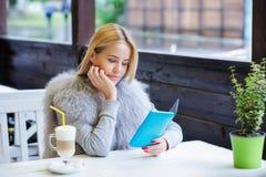 Молодая женщина наслаждаясь ее временем во время перерыва на чашку кофе Стоковые Изображения