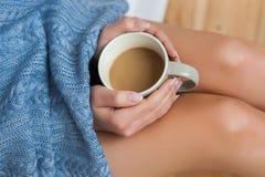 Молодая женщина наслаждаясь ее кофе пока сидящ на кровати стоковые изображения