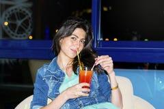 Молодая женщина наслаждаясь летними каникулами с красным спиртным коктеилем в руке Стоковое Изображение RF