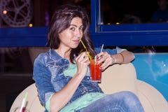 Молодая женщина наслаждаясь летними каникулами с красным спиртным коктеилем в руке Стоковая Фотография