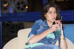 Молодая женщина наслаждаясь летними каникулами с красным спиртным коктеилем в руке Стоковые Изображения