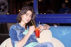 Молодая женщина наслаждаясь летними каникулами с красным спиртным коктеилем в руке Стоковые Изображения RF