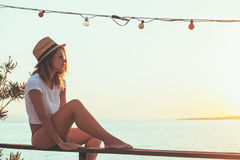 Молодая женщина наслаждаясь заходом солнца Стоковое фото RF
