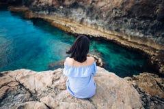 Молодая женщина наслаждаясь красивым видом на море на накидке Greco в Кипре Стоковая Фотография RF