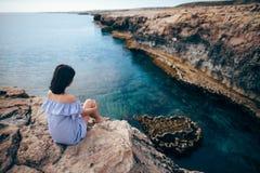 Молодая женщина наслаждаясь красивым видом на море на накидке Greco в Кипре Стоковые Изображения RF