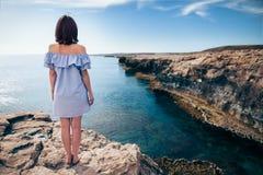 Молодая женщина наслаждаясь красивым видом на море на накидке Greco в Кипре Стоковое Фото