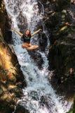 Молодая женщина наслаждаясь свежестью водопада стоковое изображение rf