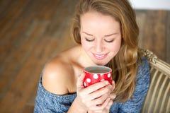 Молодая женщина наслаждаясь чашкой чаю дома Стоковое Изображение RF