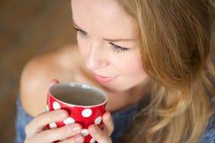 Молодая женщина наслаждаясь чашкой чаю Стоковое Изображение