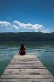 Молодая женщина на береге реки Стоковая Фотография