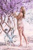 Молодая женщина на велосипеде в лесе пинка фантазии Стоковые Изображения