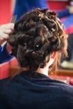 Молодая женщина на волосах парикмахера завивая Стоковое Фото