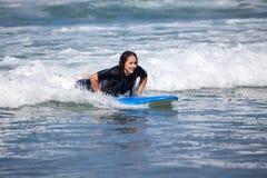 Молодая женщина на ее surfboard Стоковая Фотография