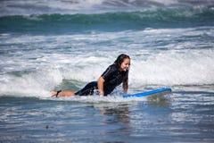 Молодая женщина на ее surfboard Стоковое Изображение