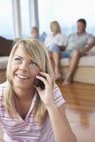 Молодая женщина на звонке дома Стоковая Фотография