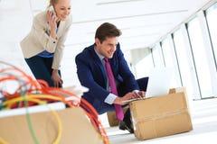 Молодая женщина на звонке пока смотрящ мужского коллеги используя компьтер-книжку в новом офисе Стоковые Фото