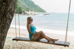 Молодая женщина на качании на пляже Стоковые Изображения RF