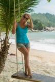 Молодая женщина на качании на пляже Стоковое Изображение