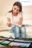 Молодая женщина на кресле, рисуя в книжка-раскраске Стоковое Изображение
