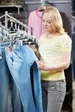 Молодая женщина на магазине одежд ходя по магазинам Стоковые Изображения RF