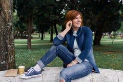 Молодая женщина на мобильном телефоне внешнем Стоковые Фотографии RF