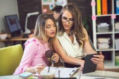 Молодая женщина 2 на офисе работая на новом дизайне Стоковое Фото