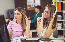 Молодая женщина 2 на офисе работая на новом дизайне Стоковые Изображения
