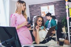 Молодая женщина 2 на офисе работая на новом дизайне Стоковое фото RF