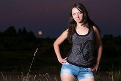 Молодая женщина на предпосылке луны Стоковые Изображения