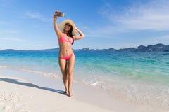 Молодая женщина на пляже принимая фото на летних каникулах телефона клетки умных, красивое взморье Selfie девушки Стоковая Фотография RF