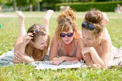 Молодая женщина 3 на пляже читая кассету Стоковые Изображения RF