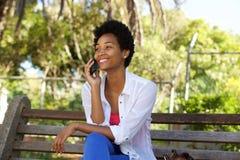 Молодая женщина на скамейке в парке говоря на мобильном телефоне Стоковые Изображения