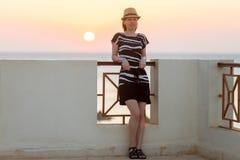 Молодая женщина на террасе с видом на море стоковые фотографии rf