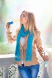 Молодая женщина надувает пузыри мыла стоковые фотографии rf