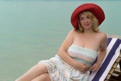 Молодая женщина на lounger пляжа Стоковые Изображения