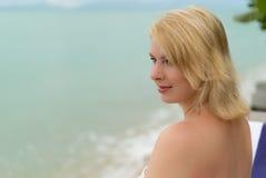 Молодая женщина на lounger пляжа Стоковая Фотография