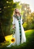 Молодая женщина нося длинное белое платье держа съемку солнцецвета внешнюю. Портрет красивой белокурой девушки с солнцецветом Стоковое Изображение RF