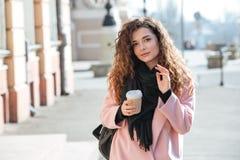 Молодая женщина нося розовое пальто идя в солнечный город Стоковое Изображение