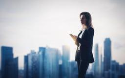 Молодая женщина нося современный костюм держа ее Стоковые Фото