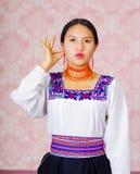 Молодая женщина нося традиционное андийское платье, смотря на камеру делая слово языка жестов для женщины Стоковое Фото