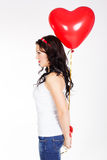 Молодая женщина дня валентинки красивая нося красное платье и держа красные воздушные шары Стоковое Фото
