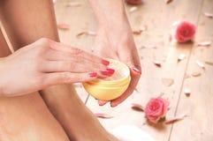 Молодая женщина добавляя сливк к ее красивым ногам Стоковые Изображения